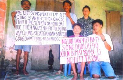"""Bà mẹ liệt sỹ Nguyễn Thị Tám, cùng 4 Phật tử kêu oan cho Đại đức Thích Nguyên Kiên. Mẹ Tám cầm tấm biểu ngữ : """"Người dân Việt Nam sống dưới chế độ XHCN bị mất Nhân quyền nghiêm trọng"""""""