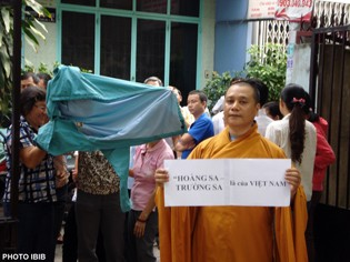 """Venerable Thich Vien Hy holds a poster: """"The Paracel and Spratly islands belong to Vietnam"""". Behind him, plain clothed Security agents hide their faces to avoid being recognized by demonstrators on the streets (Photo IBIB)"""
