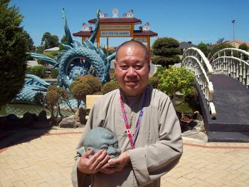PERSECUTED: A Buddhist monk holds a desecrated statute at his temple in Marangaroo, Western Australia, January, 2009. He believes Hanoi was behind the attack. (Scott Johnson)