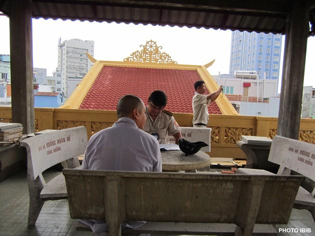 """Les fonctionnaires locaux prennent des photos des travaux de renovation sur la terrasse de la Pagode Giac Hoa, le 22 mars 2012, et dresse un rapport sur les """"violations des règles de construction"""" (Photo IBIB)"""