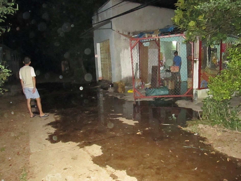 Foul-smelling water runs down the road outside Huynh Ngoc Tuan's home