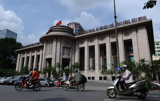 Motorcyclists ride past the State Bank of Vietnam headquarters in downtown Hanoi on July 6, 2012. Lawmakers and activists called for the United States to press Vietnam to free dissidents and allow greater religious freedom as the two nations hold talks on human rights (Photo By Hoang Dinh Nam)