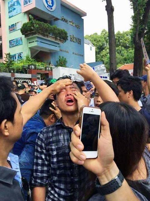 Đào Nguyên Anh đang được những người biểu tình khác giúp rửa mắt sau khi bị xịt hơi cay