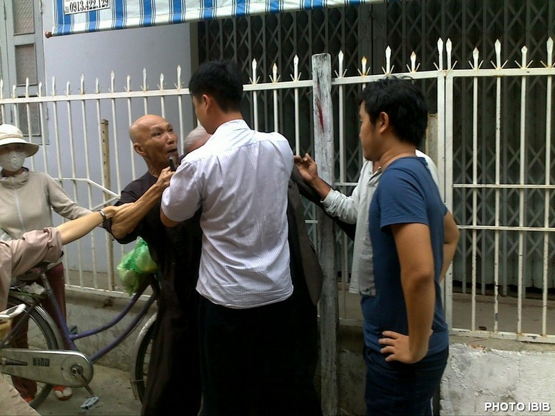 He grabs Thich Thanh Quang's neck and presses him against the railings. Photo IBIB 17.8.2012
