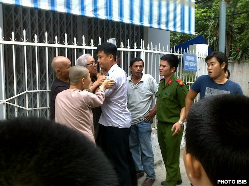 Security Police watch as the youths assault Thich Thanh Quang and Le Cong Cau. Photo IBIB 17.8.2012